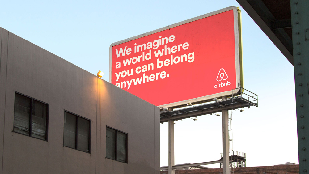 """Billboard ad for Airbnb saying """"We imagine a world where you can belong anywhere."""""""