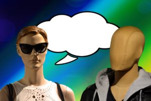 Woman mannequin with sun glasses and speech bubble above her head talking to male mannequin who has no face telling him the truth about his brand